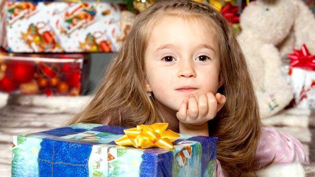 маленька дівчинка біля подарунка